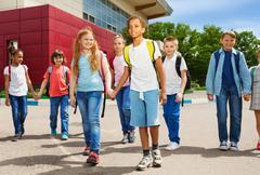 Children holding hands carry rucksacks and walk - stock photo