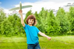 Small cute boy holds white airplane toy alone Stock Photos