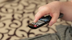 Channel surfing with remote control in hand Stock Footage