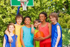 International friends stand after basketball game - stock photo