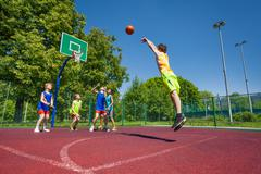 Boy performs foul shot at basketball game Stock Photos
