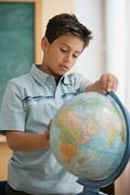 Schoolboy looking at globe - stock photo