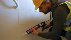 Handyman filling in tiles Stock Footage