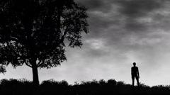 Man standing in a field against dark skies Stock Footage