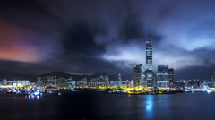 Night Hong Kong city skyline reflects in water of harbour. 4K urban background - stock footage