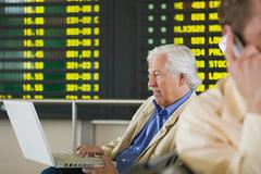 Men telecommuting in airport - stock photo