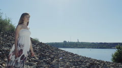 Woman standing on rocky coastline behind the town Stock Footage