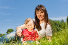 Small cute baby and his mummy sitting in meadow - stock photo