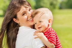 Portrait of baby and his mummy in the green meadow - stock photo