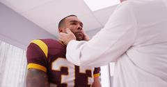 Mid aged doctor checking football player's sports neck injury Stock Photos