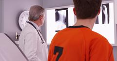 Medical doctor reviewing sports athlete's neck injury xrays Stock Photos