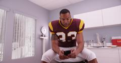 African-american football player texting while waiting in a hospital room - stock photo