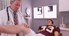 College sports athlete with mid aged doctor examining knee injury Stock Photos