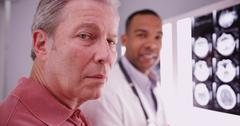 Senior male patient looking at camera with young medical practitioner Stock Photos