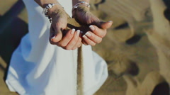 Woman with sand falling through her hands on beach Stock Footage