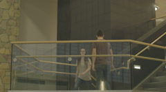 Young Man and Young Woman Cross Paths on Stairwell Stock Footage
