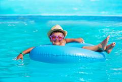 Cute boy wearing hat, glasses in inflatable ring - stock photo