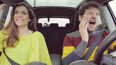 Woman laughing after slapping in face boyfriend while driving car Stock Footage