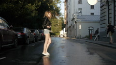 Pretty girl in shorts walking down the street after a rain. - stock footage