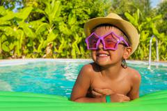 Happy boy in shaped sunglasses on green airbed - stock photo