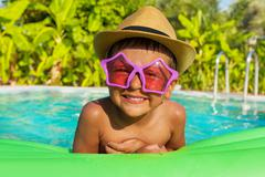Boy in sunglasses on green airbed, swimming  pool - stock photo