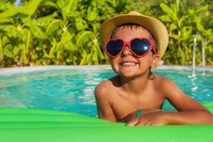 Boy in heart-shaped sunglasses on green airbed - stock photo