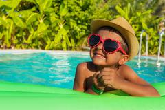 Cute boy on green airbed in the swimming pool - stock photo