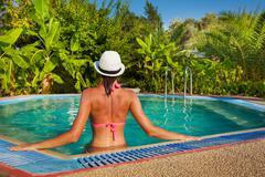 Young woman wearing bikini in small pool - stock photo