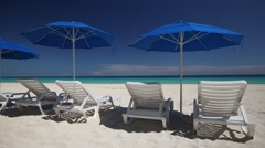 Beach with blue sun umbrellas and white plastic beds Stock Footage