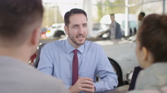 4K Happy couple in car dealers shake hands with salesman & take key to new car Stock Footage