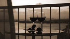 Two glasses with red wine on balcony with blowing curtains Stock Footage