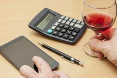 Calculating wine drinker at his desk using his smart phone Stock Photos