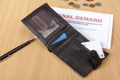 Final demand letter on a desk with a wallet Stock Photos