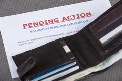Open wallet laying across a final demand letter Stock Photos
