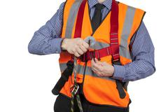 Building Surveyor in orange visibility vest attaching lanyard to safety harne - stock photo