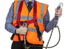 Building Surveyor in orange visibility vest securing safety harness lanyard - stock photo
