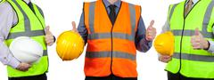 Three site surveyors in high visibility vests giving the thumbs up - stock photo