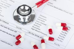 Red stethoscope and pill capsules laying on medical form Stock Photos