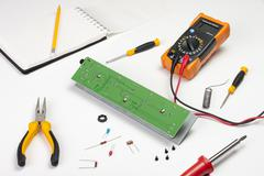 Busy electronics engineers workstation showing a pcb and tools - stock photo