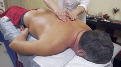 Masseuse press backbone of adult fat man. Therapeutic massage. Medium shot Stock Footage
