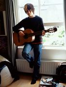 Boy playing acoustic guitar Stock Photos
