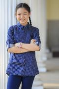 portrait of thai 12s years girl wearing blue shirt standing out door with too - stock photo