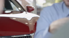 4K Close up on hands of salesman in car dealership giving key to new owner.  Arkistovideo
