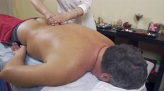 Masseuse hands press backbone of adult fat man. Remedial massage. Medium shot - stock footage