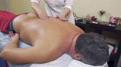 Masseuse rubdown backbone of adult fat man. Therapeutic massage. Medium shot Stock Footage