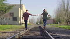 Cute Couple Hold Hands And Balance On Train Tracks Stock Footage