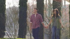Cute Young Couple Go For A Walk In The Park On A Sunny Day Stock Footage