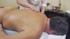 Professional masseuse make healing massage of back to adult fat man. Medium shot Stock Footage