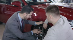 4K Salesman in car dealership showing customer new car & shaking hands on a deal Stock Footage