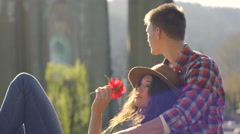 Attractive Young Couple Relax In Park, Take Turns Smelling A Flower Stock Footage